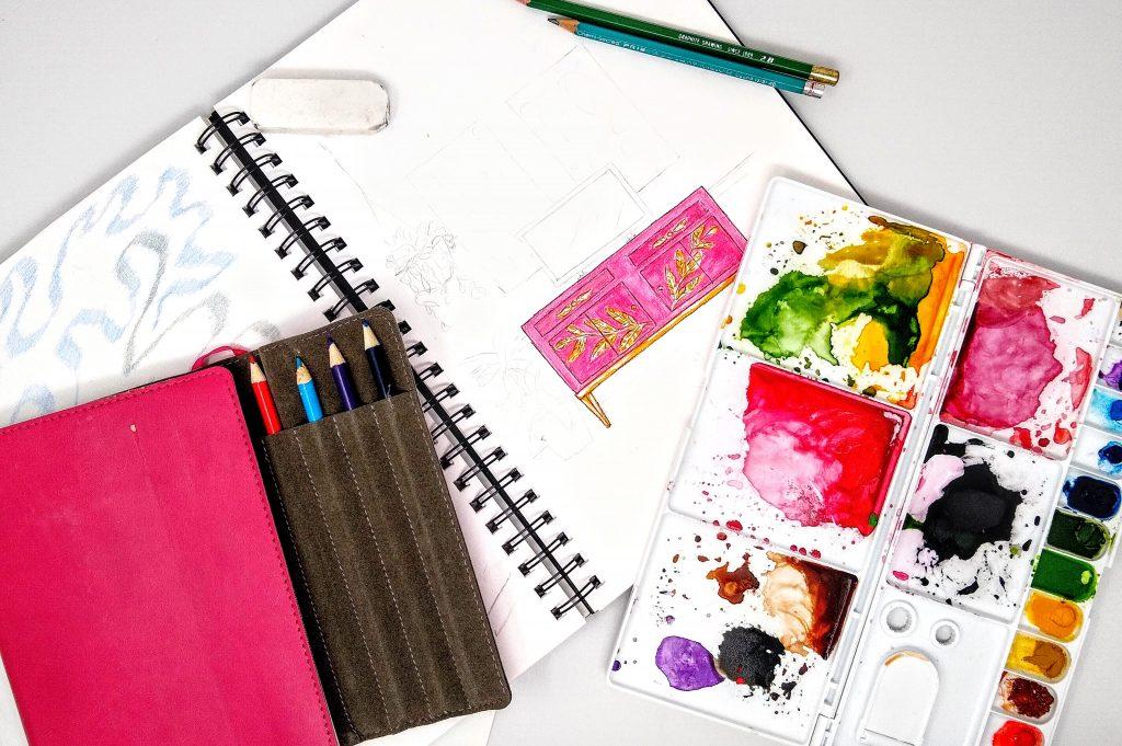 Inside sketchbook, paint pallette, and travel sketchbook